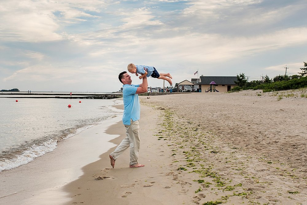 Connecticut family photographer. Father spinning son in air at the beach during lifestyle family photography connecticut