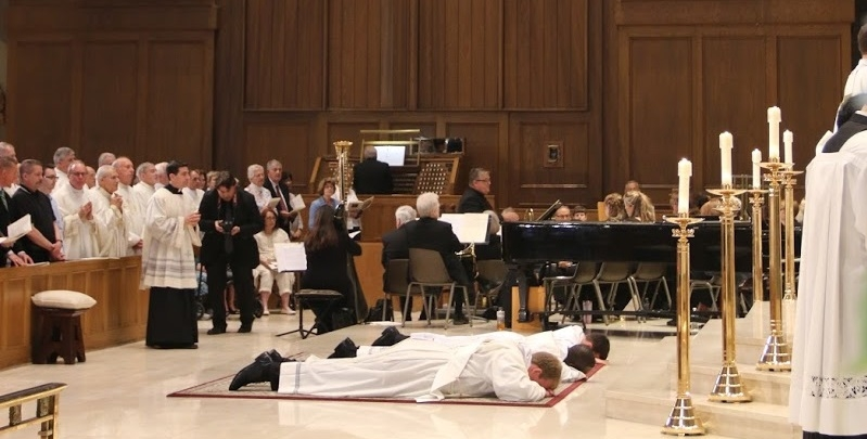 Father Brian Morris, a native of Our Lady of Mercy Parish, Father Joseph Brice, and Father Stephen Battey lay prostrate during the Ordination Mass, June 2017.
