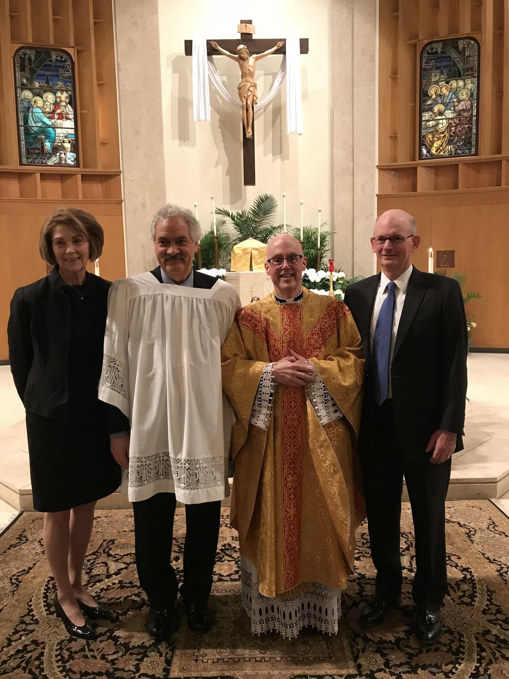 Following the Easter vigil, the newly Baptized and Confirmed Al Behbehani wears his White Baptismal gown and poses with his sponsors, Mary Anne and Rod Weaver, and Fr. Healey, OLM Pastor.