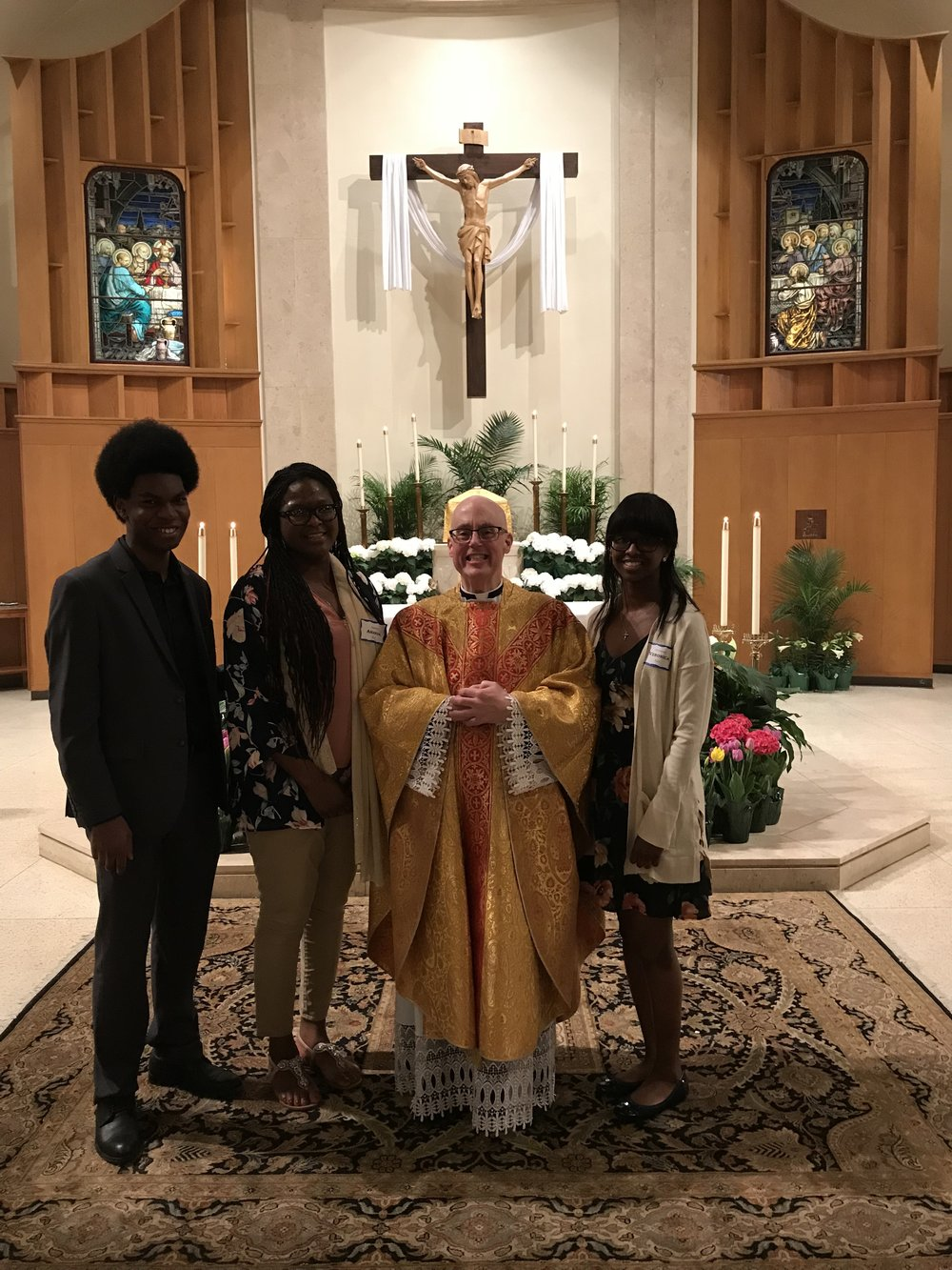 Following the Easter vigil, the newly Confirmed Joanne and Gerrianne Exil pose with their sponsor, Kelsey Exil and Fr. Healey.