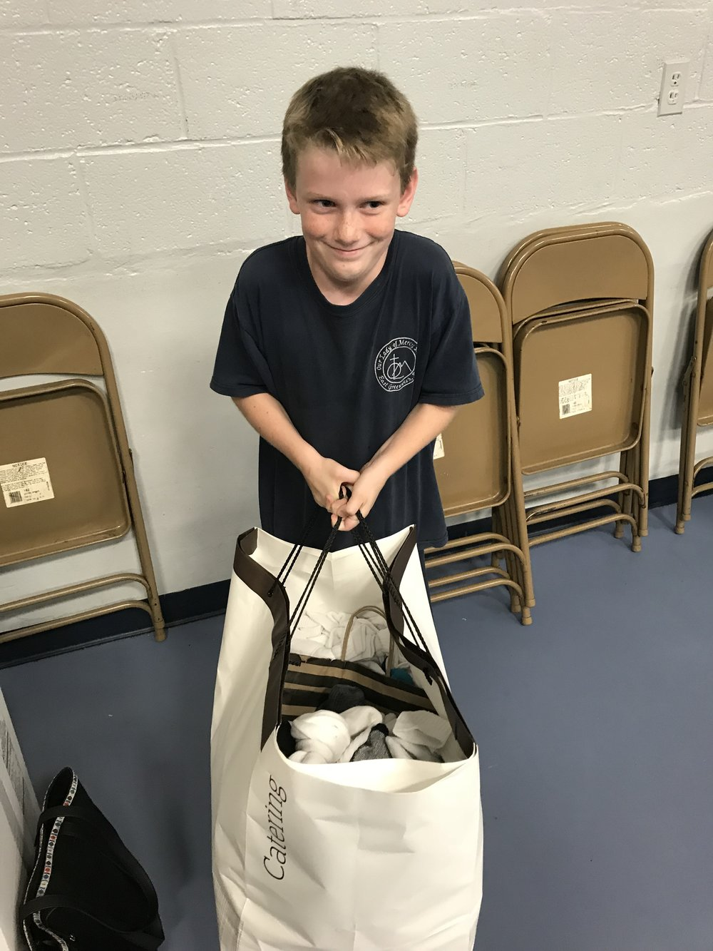 OLM School 4th Grader Joseph Ferris helps during the Act of Mercy, Socks & Sandwiches for the Homeless!