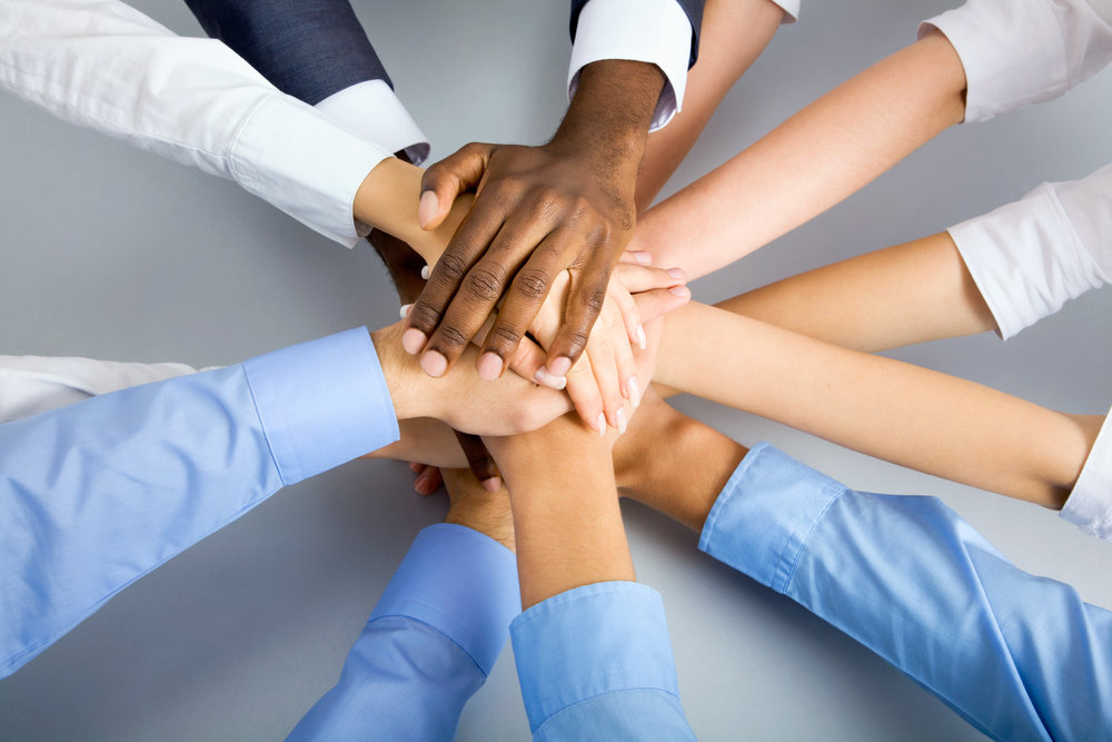 stock-photo-international-business-team-showing-unity-with-their-hands-together-114113191.jpg