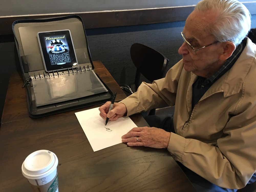 Art Flynn, former Chief Inspector at Norwood and the first man to drive a production Trans Am, adds his signature to the Norwood commemorative poster.