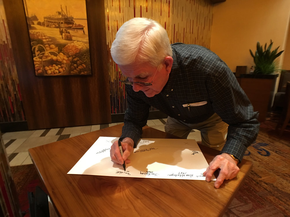 Dan Wall, former Head of Payroll at Norwood Assembly, signs the signature panel at a Norwood alumni luncheon.