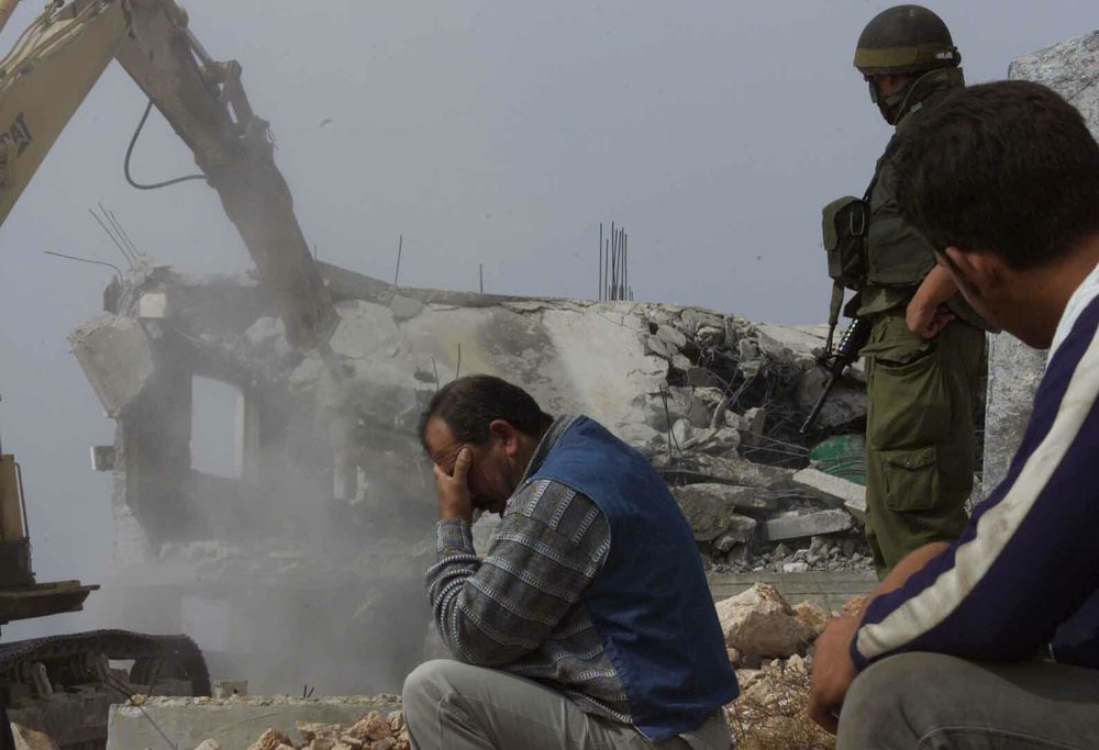 A-Palestinian-man-cant-look-as-his-home-is-demolished.jpg