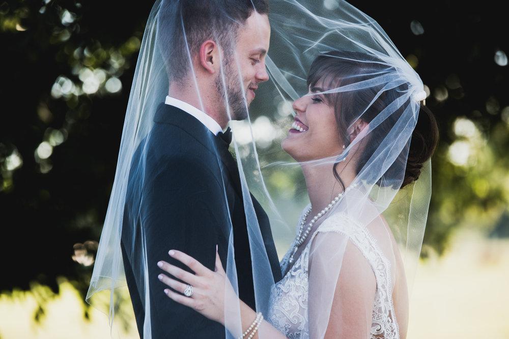 Bride throws veil over groom