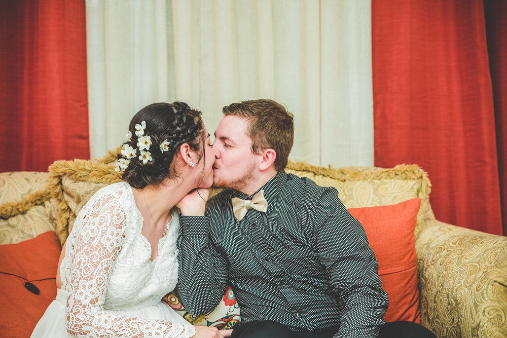 Newly Weds share a Kiss on a couch
