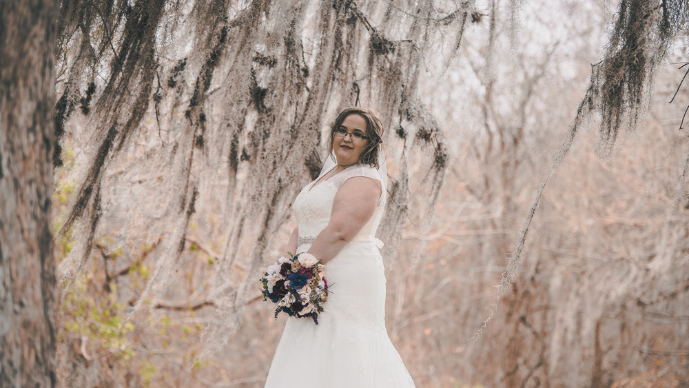 Bride posing near a willow tree