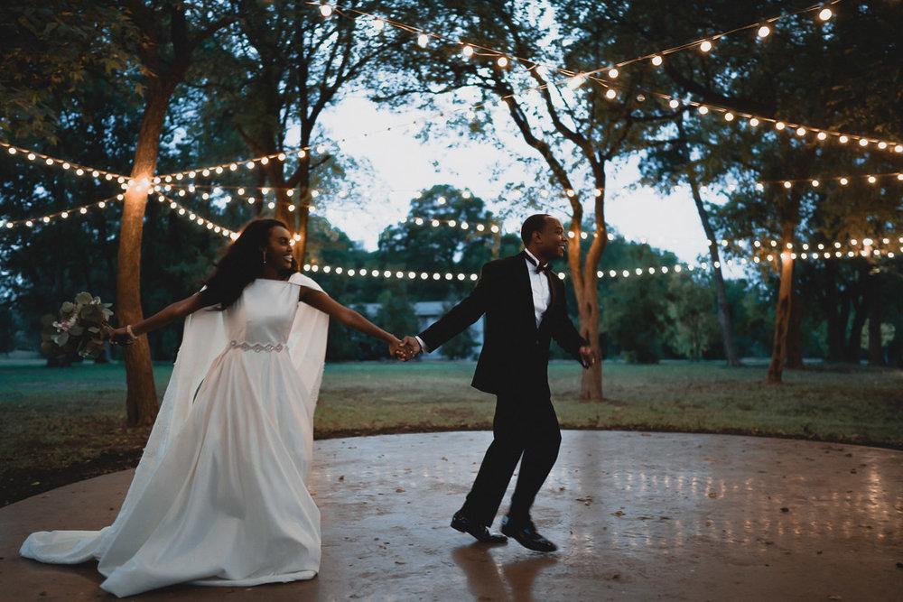 Bride and Groom Running under String lights