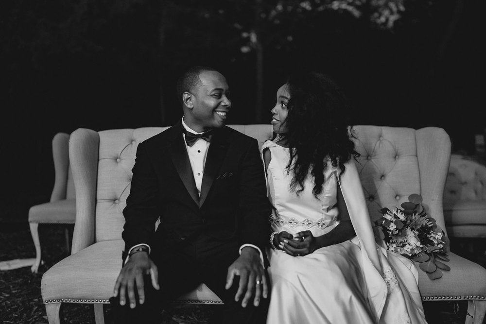 Bride and groom sitting on a couch in a forest