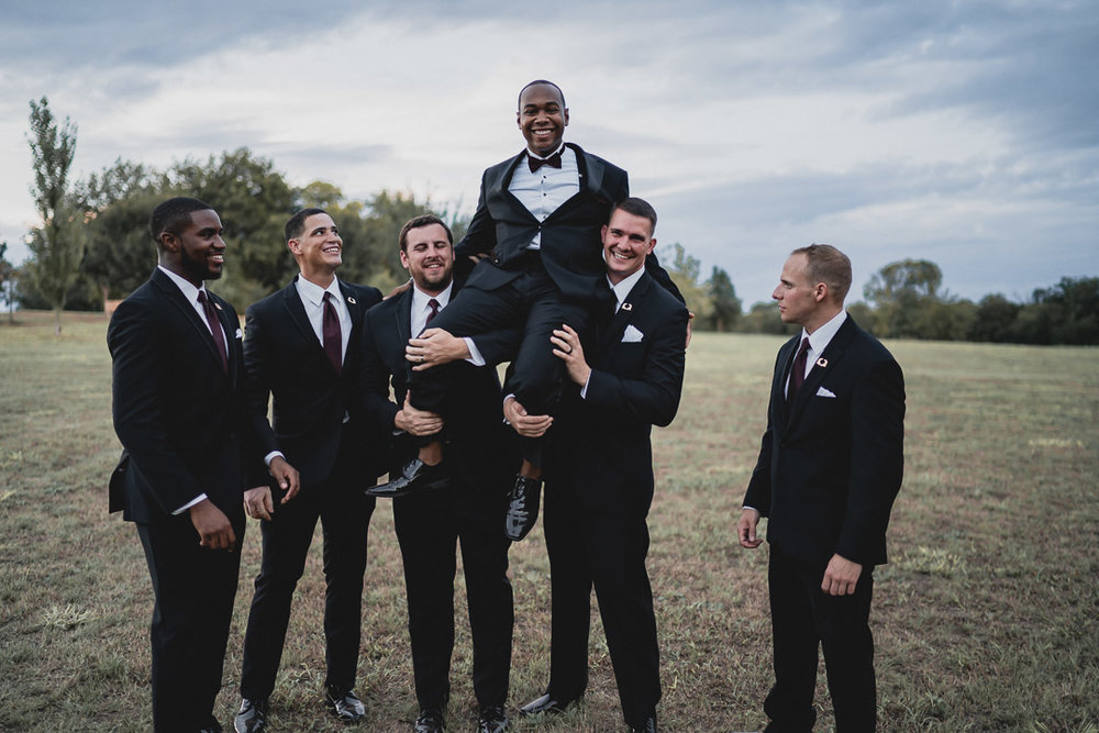 Groomsmen picking up the groom