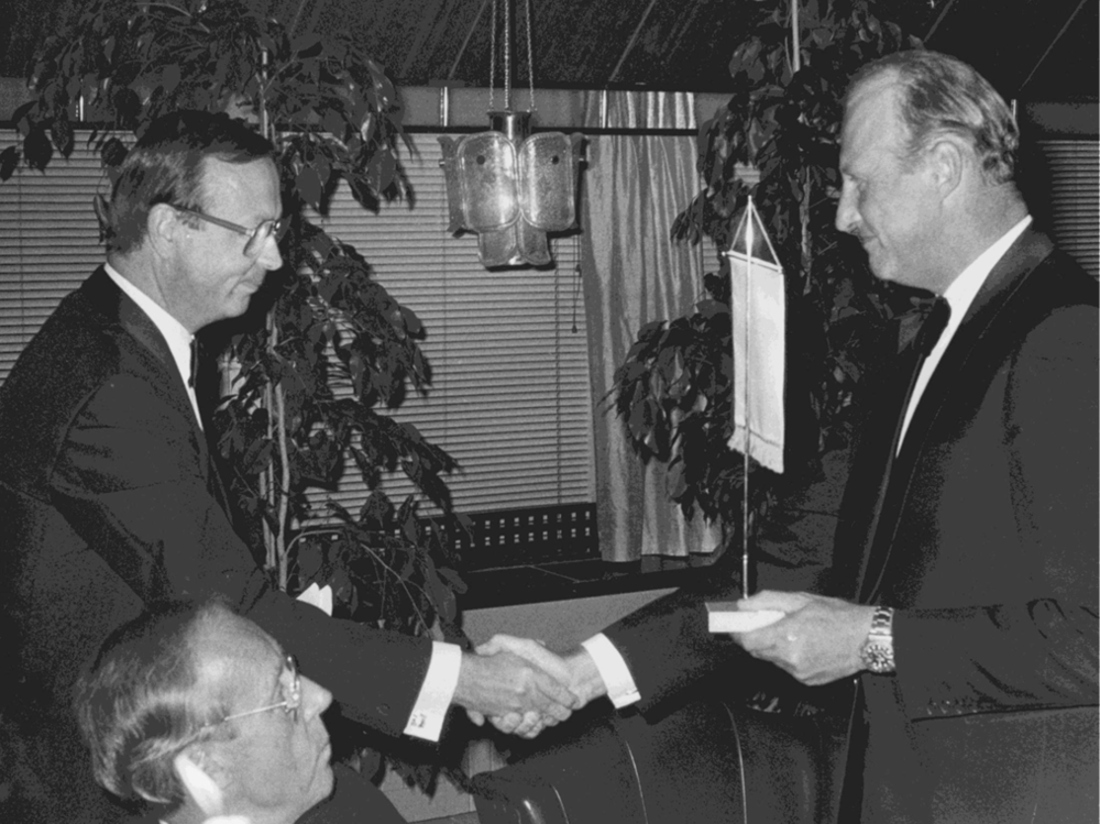 Ordf. Stig Simelius overrekker foreningens standard nr. 1 til HKH Kronprins Harald på festmiddagen på Palace 5.9.1985. Minister Tankmar Horn bevitner seremonien.
