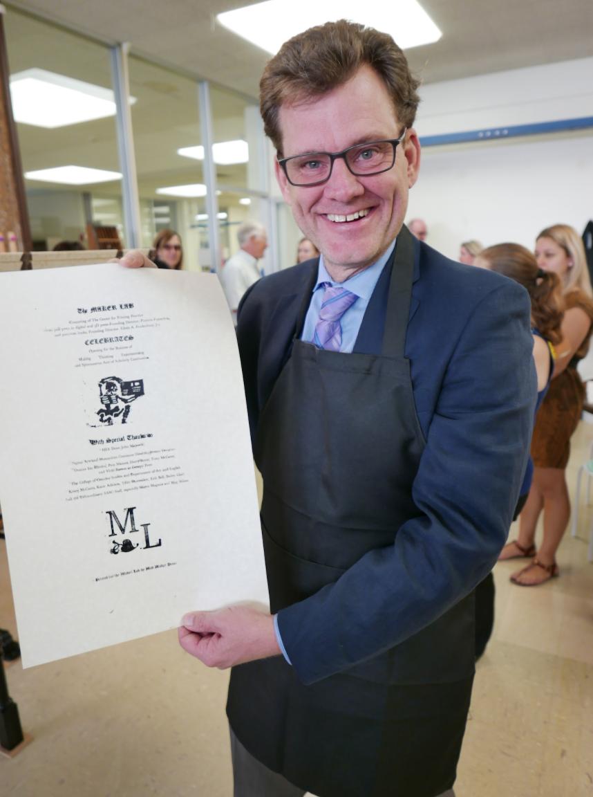 Dean John Majewski shows off his commemorative print fresh from the printing press.