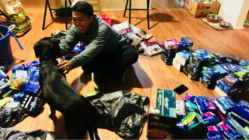 """A Phi Alpha Delta member pets a dog at a student's home in Isla Vista while getting donations ready for drop-off after the """"UndAWARE"""" event."""