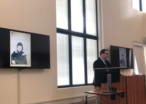 """Peter Manseau, curator of American religious history at the Smithsonian Institution, displaying one of the first """"Spirit Photographs"""" during his talk at UC Santa Barbara."""