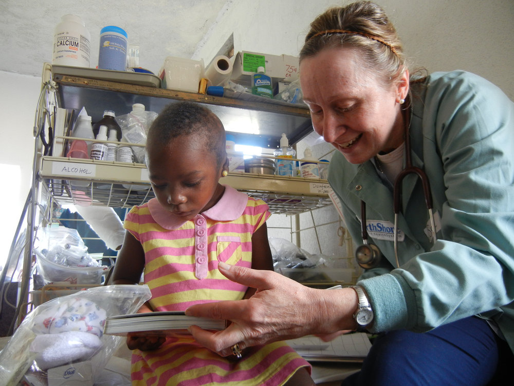 Sue Walsh reads to a Haitian girl displaying severe burn marks from a previous accident.
