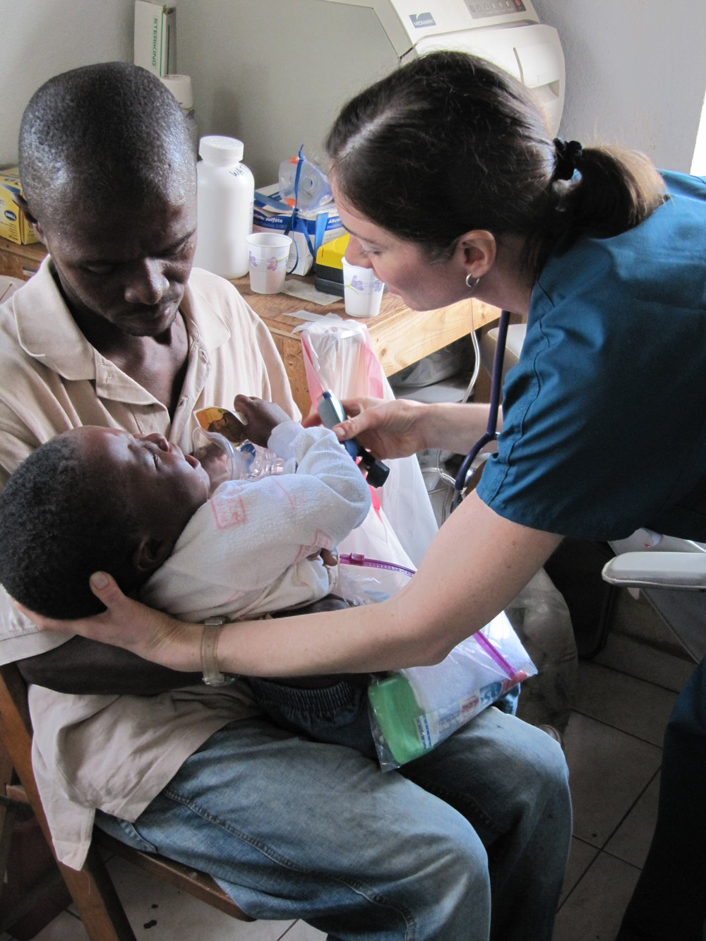 Medical professional, Dawn Ribnek works with a Haitian family in the MTM clinic in Gramothe, Haiti.