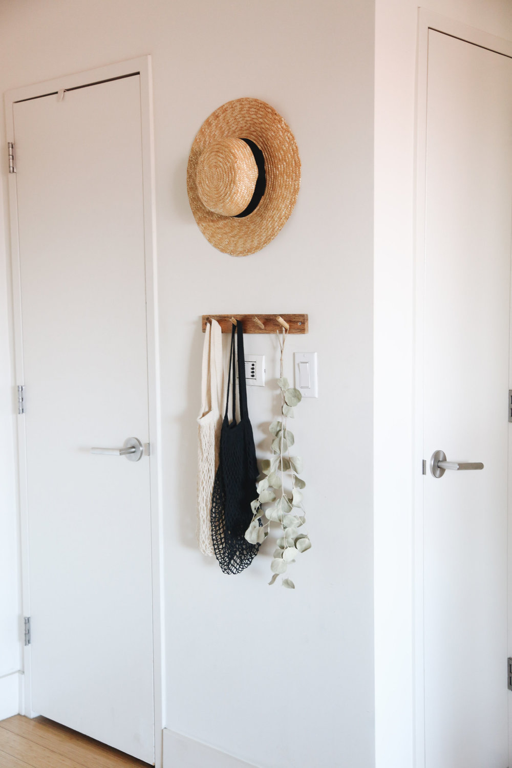 Since the entry can be seen from pretty much every other spot in our home, I kept it neutral and simple, hanging my favorite hat, a wooden clothes rack, woven bags to grab on my way out the door for groceries, and, because there wasn't room for plants, I also hung some dried euculyptus.