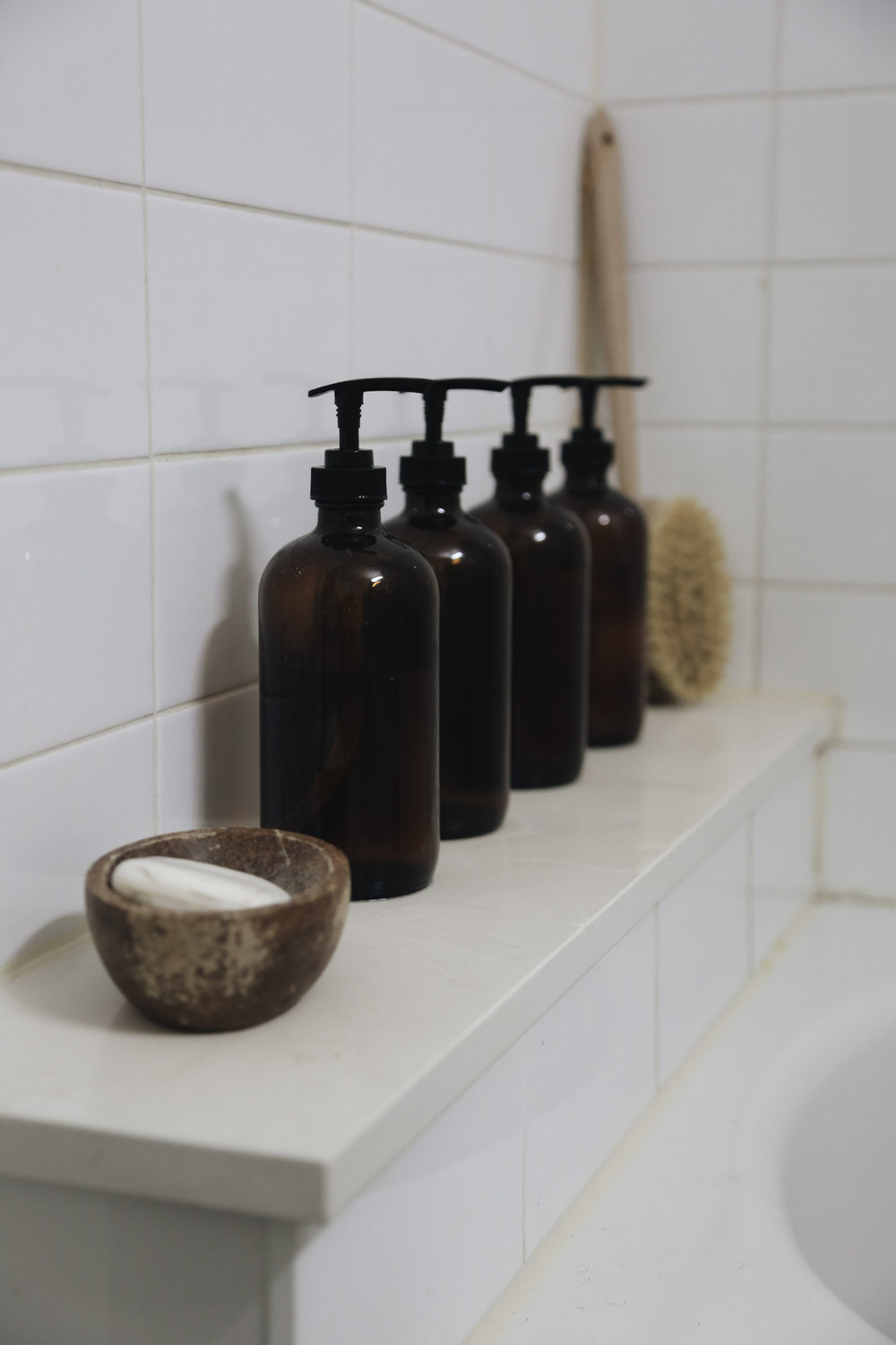 To keep our small bathroom from feeling too small, we kept decor to a minimum. Our daily soaps were transferred to plain  brown bottles , and along with a small wooden bowl used as a soap dish ( similar option ) and  body brush , were the only things kept out. All other products were kept under the sink.