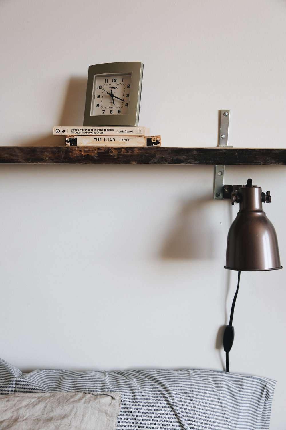 A clock I've had since childhood, some old books, our DIY wooden shelf and Ikea wall lights, since we had no side tables for small lamps.