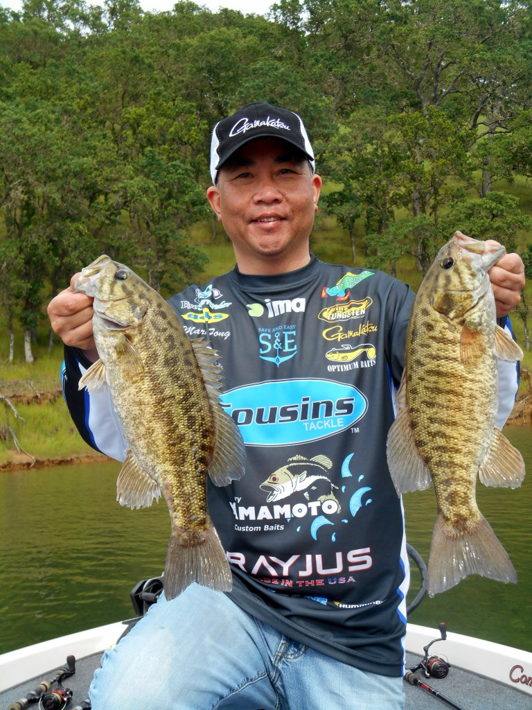 The author happily shows off a couple of beauties. Popper topwater lures, which mainly imitate smaller baitfish, should always be in your tackle box as a potential bass catcher. (MARK FONG)