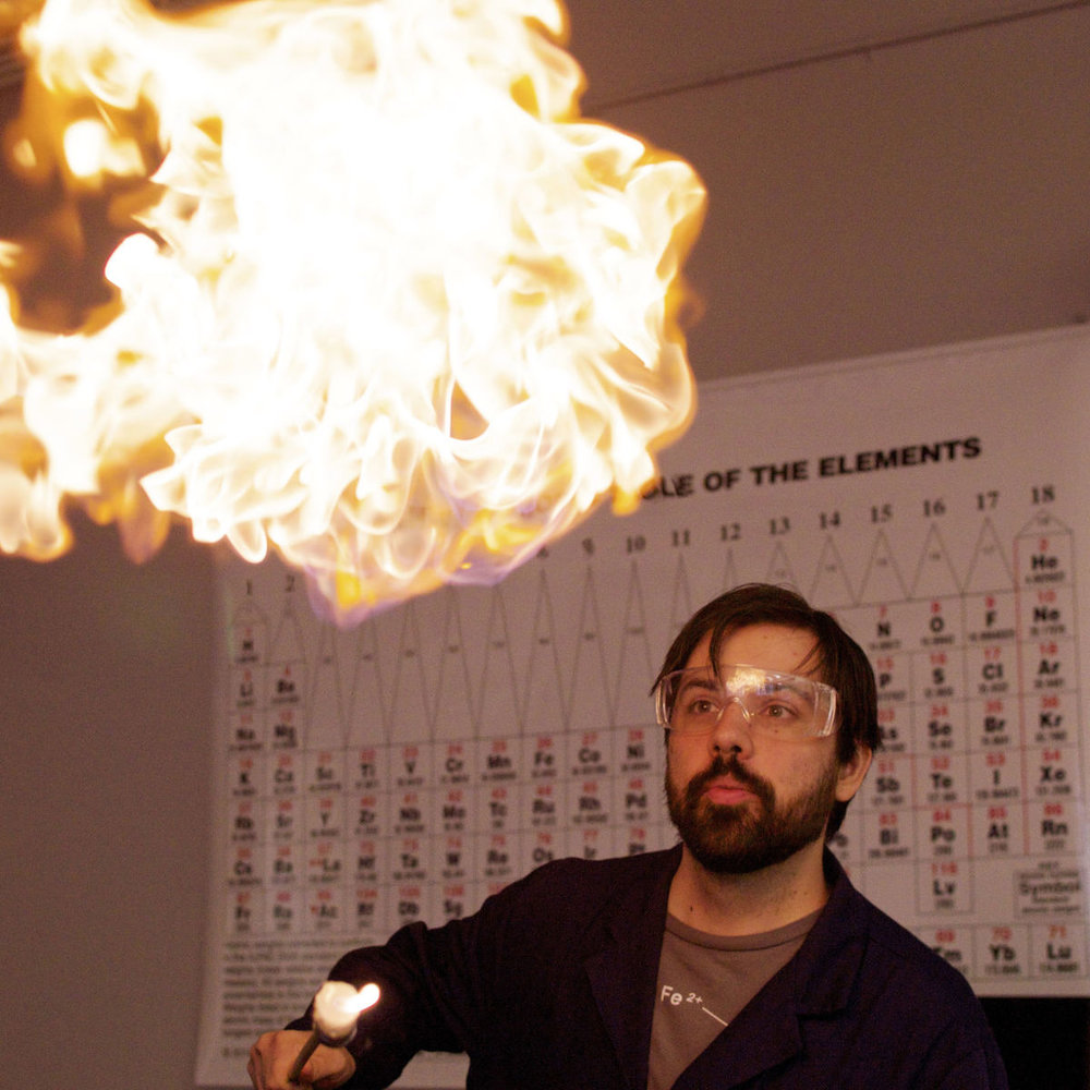 Eric Camp performing a chemistry demonstration. This specific demosration involves igniting a balloon filled with hydrogen. This produces a small explosion.