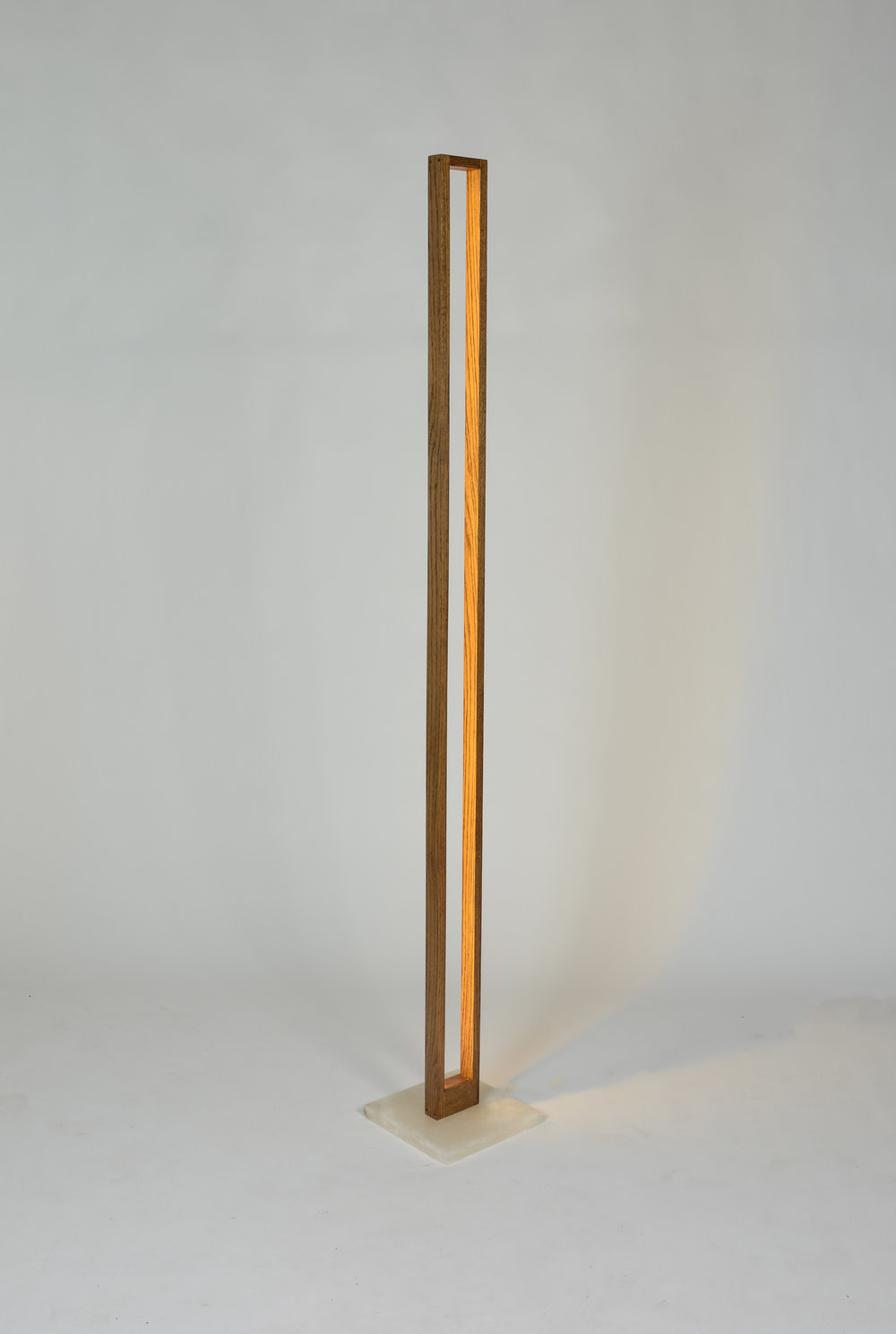 BEACON - Slender floor lamp made with oak wood, alabaster, and warm dimmable LEDs that are rated for 30,000 hours. The LEDs are oriented to provide a back-lit illumination, providing a warm ambience to a room environment.Dimensions: 64