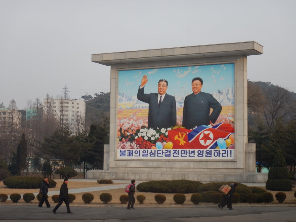 Hand-painted propaganda murals like this one in Pyongyang, featuring Kim Il-sung and Kim Jong-il smiling in a field of flowers, are commonplace in many larger North Korean cities. (Photo by Ethan Jakob Craft.)