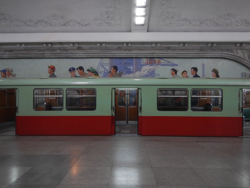 An empty subway car parked in the Pyongyang Metro's Puhung Station, found in the southern part of the city. Visible behind the car is a tile mosaic depicting the life of average North Korean workers. (Photo by Ethan Jakob Craft.)