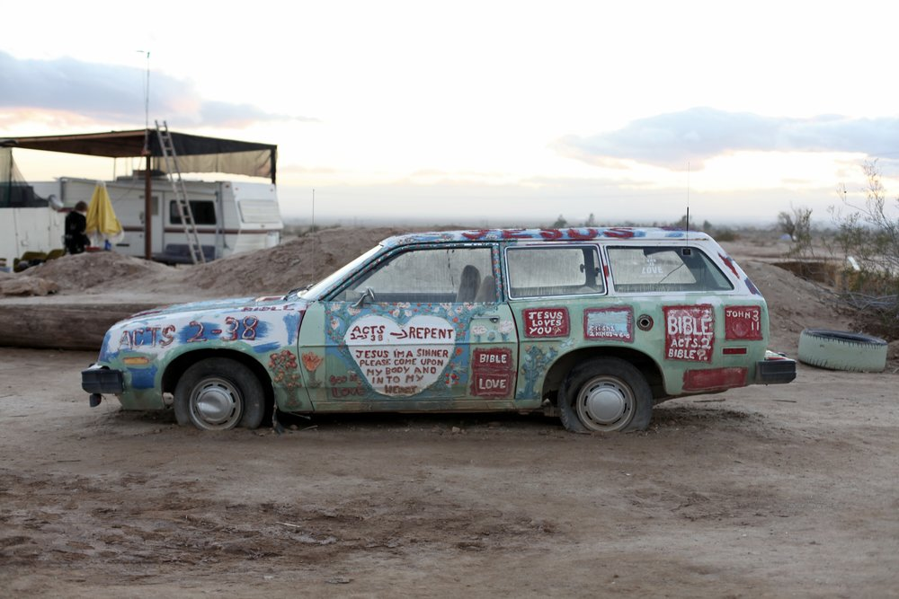 A Ford Pinto station wagon hand-painted with Bible verses is one of many such cars surrounding Salvation Mountain in Slab City, Calif. on Jan. 6, 2017. (Photo by Ethan Jakob Craft.)