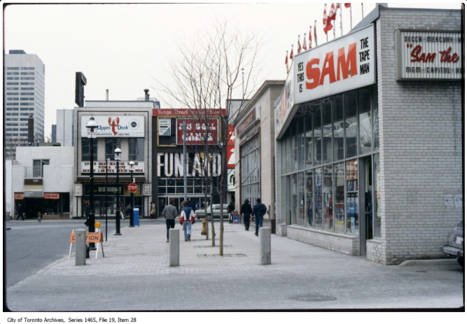 Gould Street looking west to Yonge, 1980s, featuring Sam the Tape Man, an additional Sam the Record Man property. Ryerson's modern SLC library building now occupies the space.