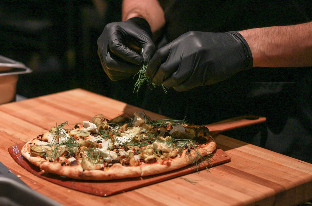 "Sous chef Dan Raznavi deftly tops off the Chorizo and Artichoke pizza with a generous helping of fennel fronds. The Chorizo and Artichoke features unique meat and dairy substitutes such as their ""soyrizo"" bits and cashew mozzarella. (The Unaffiliated Press/Kayla Zhu)"