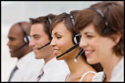 Customer service representatives smiling with headsets on talking to people on the phone - NCA Alarms Nashville TN