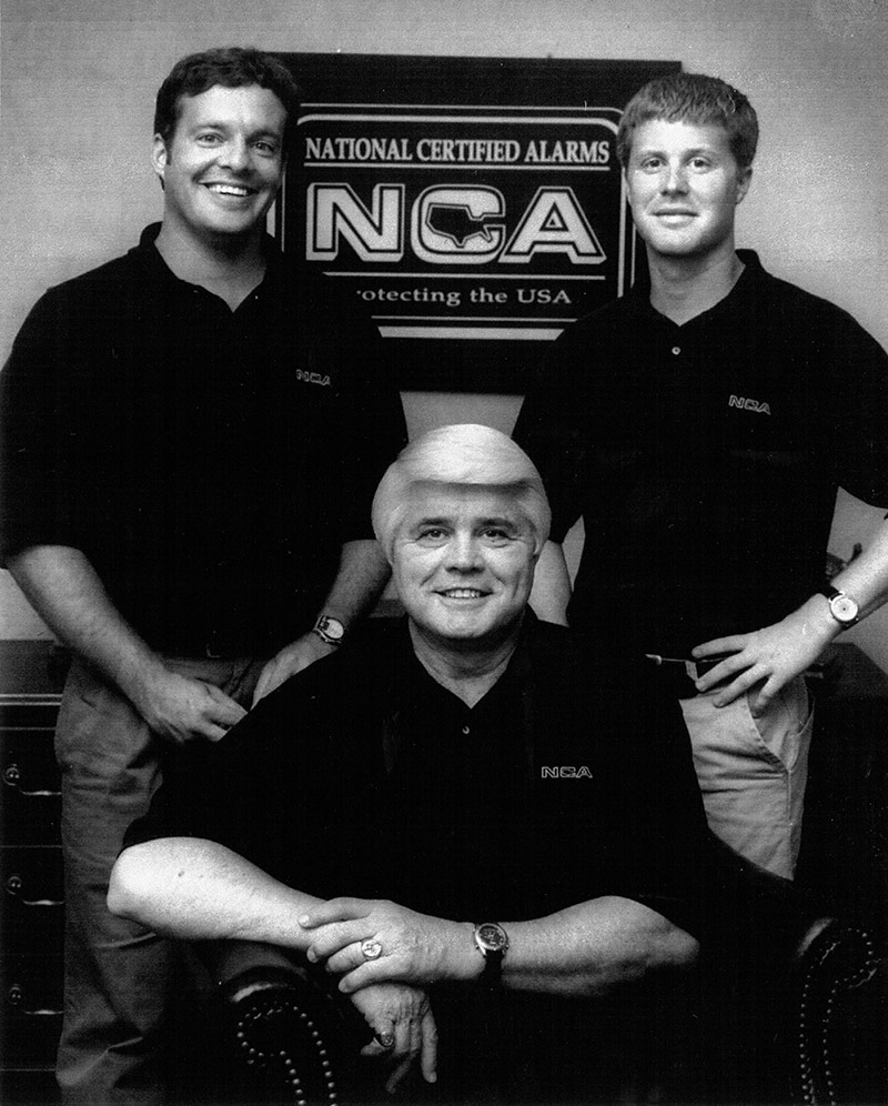 Jack Cothren, Jimmy Stein and Shooter Stein in front of sign with the company logo in December 1997 - NCA Alarms Nashville TN