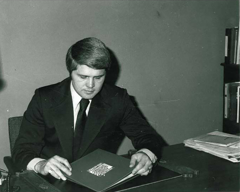 Jimmy Stein in 1974 sitting looking at a folder portfolio at an office desk - NCA Alarms Nashville TN