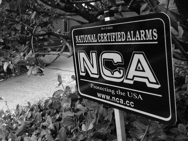 NCA Alarm sign displayed amongst the greenery by a sidewalk with the name, logo and website address - NCA Alarms Nashville TN