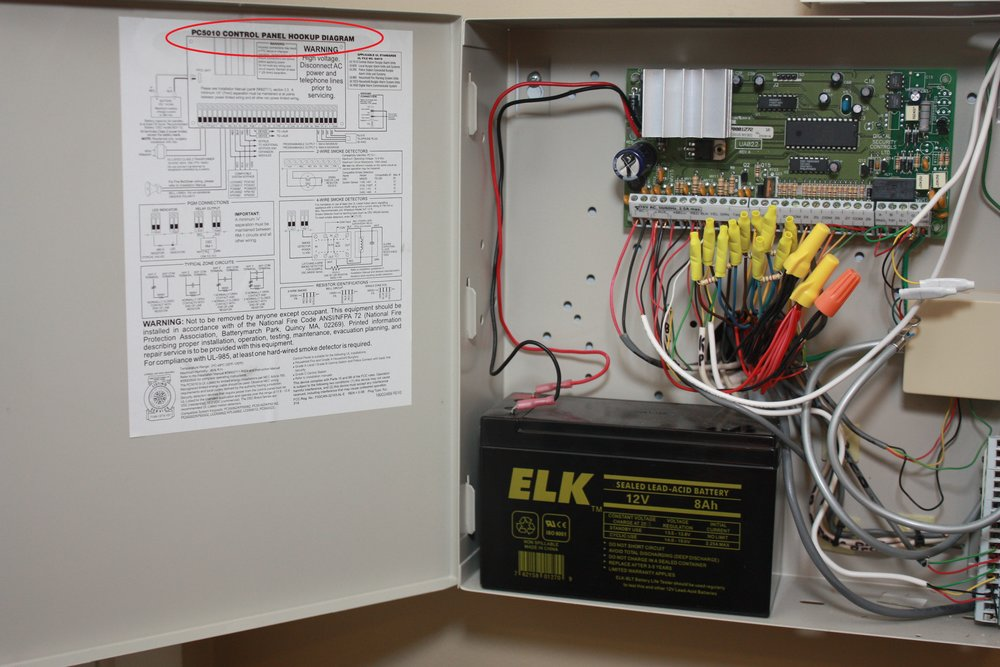 Inside the 5500 DSC Custom Alpha alarm control box displaying the schematic and circuit board - NCA Alarms Nashville TN