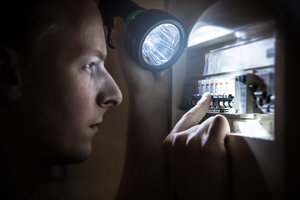 Picture of a person inspecting a fusebox