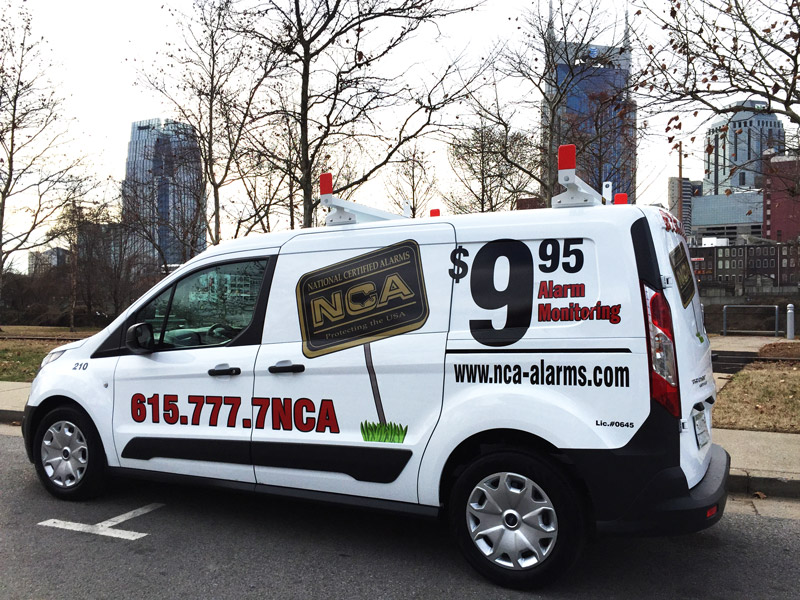 Six white NCA services vans parked, displaying company information on the sides - NCA Alarms Nashville TN