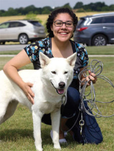 A woman with glasses kneels to pet her white dog