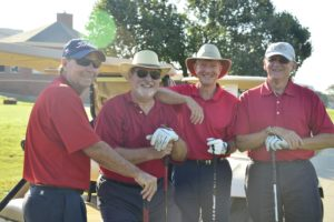 A team of four men dressed in red polo shirts, holding golf clubs
