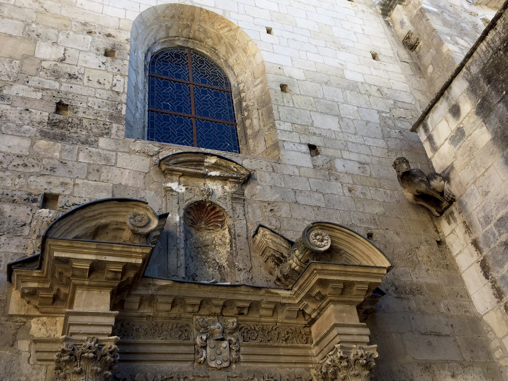 Entrance to Saint-Honorat church. Check out the grotesque at top right. Gargoyles have waterspouts, grotesques do not.