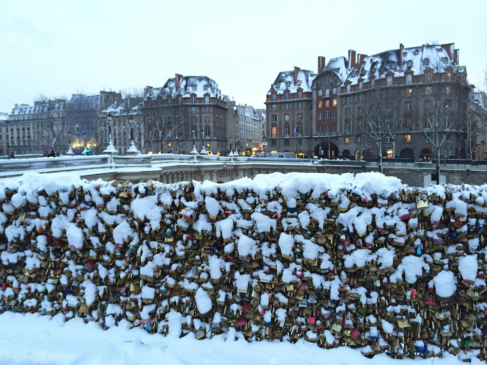 "Around the equestrian statue of Henri IV on Pont Neuf, the snow ""almost"" hides the visual assault of a plethora of love locks."