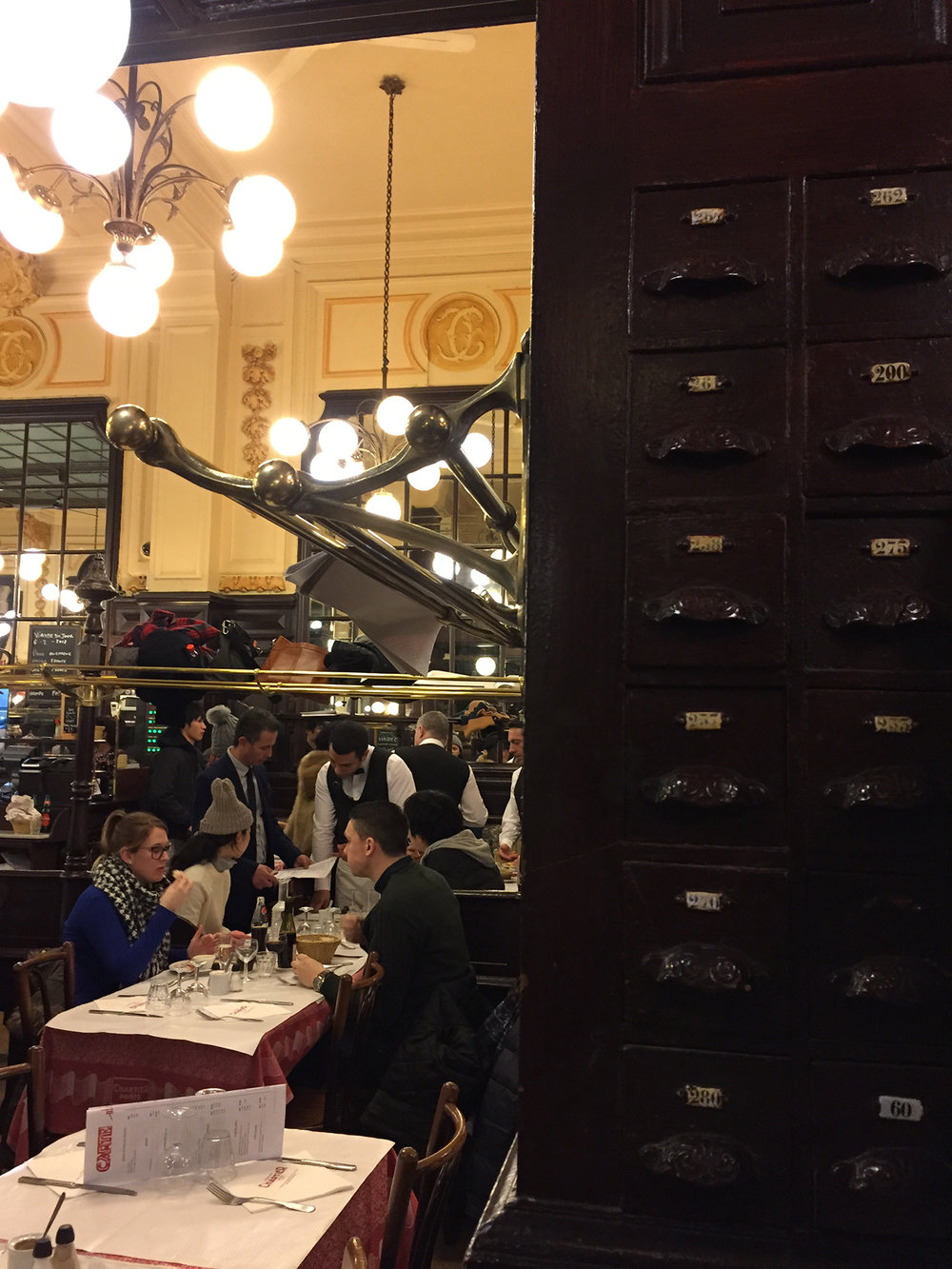 We were seated next to a bank of napkin drawers. I was very tempted to open one of them. Should have... Brass racks above the tables allow patrons to stow purses and coats.