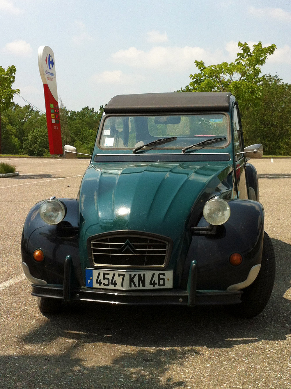 "Over the years, I've noticed a one-of-a-kind 2 CV often parked at Carrefour or Intermarché. The car is mostly dark green but has gone through several paint ""upgrades:"" on a photo I took in 2014, the front fender on the passenger side was cream instead of black."