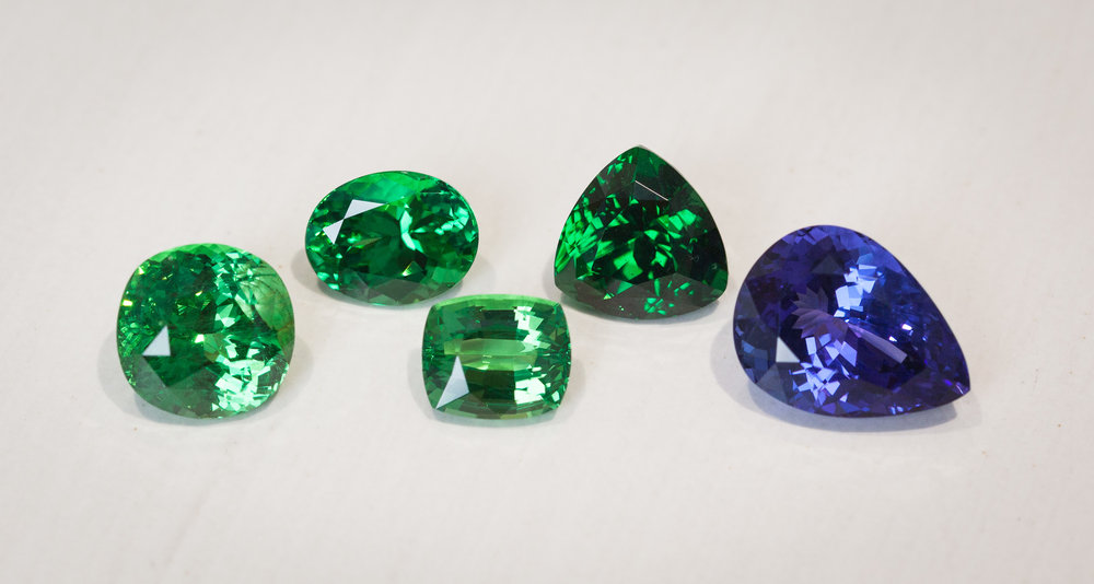 Left to right: 4.8ct Tsavorite, 3.0ct Tsavorite, 2.4ct Tsavorite, 4.5ct Tsavorite and 6.8ct Tanzanite