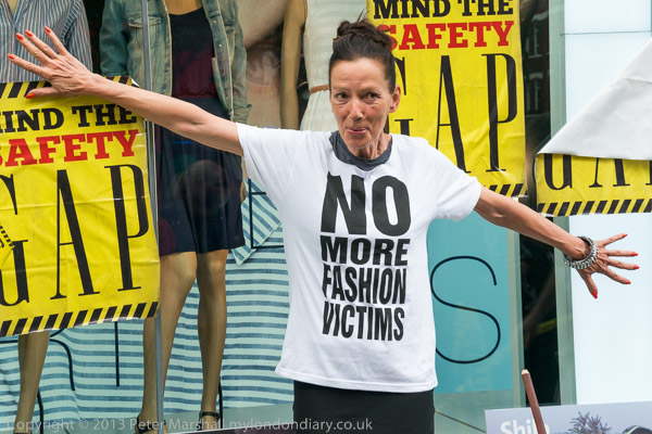 Katharine Hamnett standing in front of a Gap store window wearing her 'No More Fashion Victims' t-shirt.