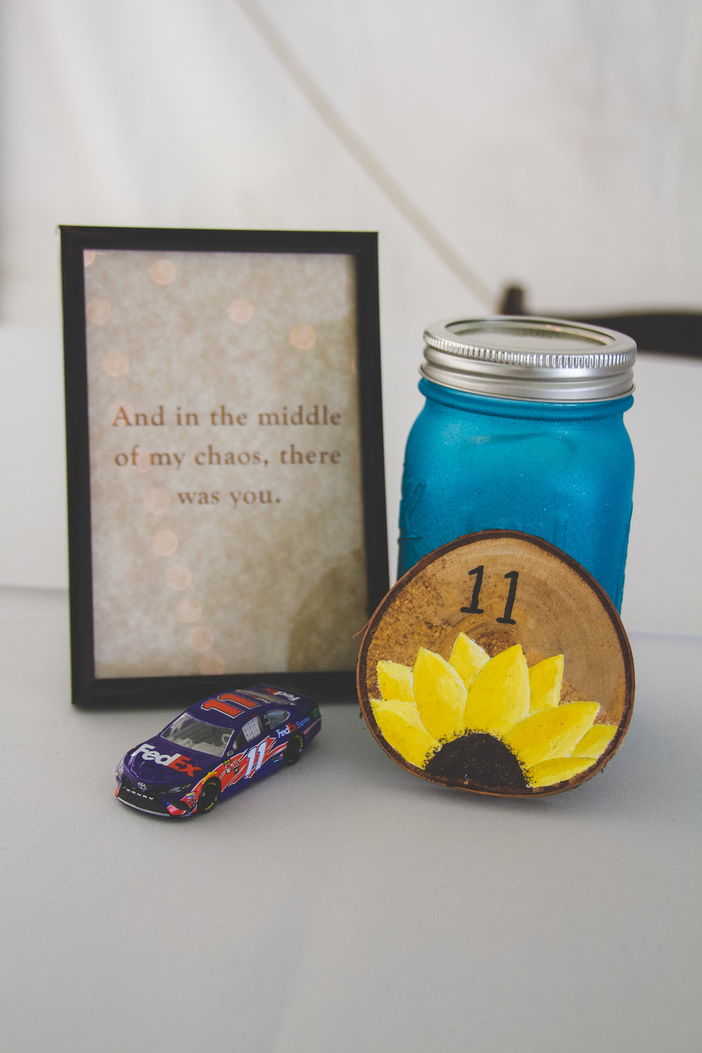 Each table featured blue Mason jars, a different quote, toy car, and hand painted table number.