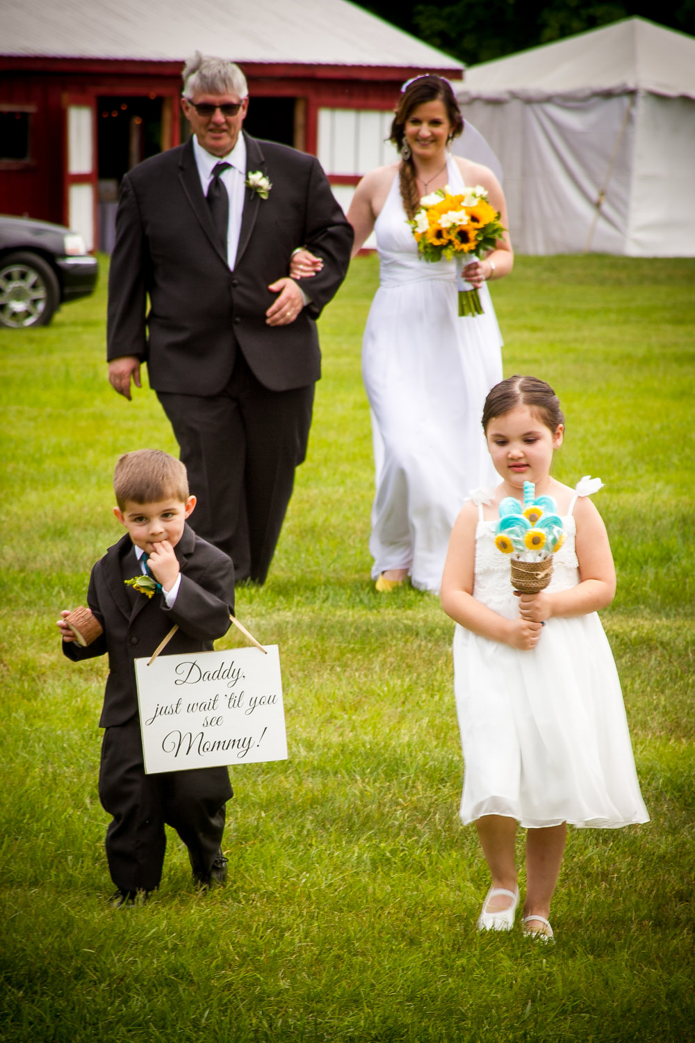 The smiling Bride makes her escorted entrance, as the flower girl and ring bearer lead the way.