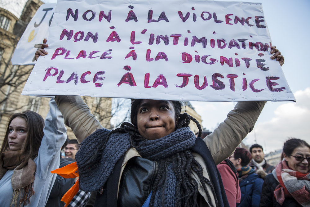 A protestor holds up a sign demonstrating against police brutality at a rally at Republique in Paris, France on February 18, 2017.